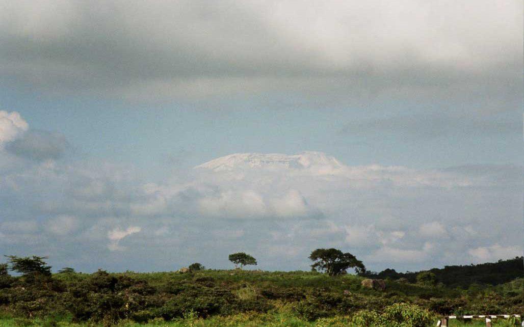 Arusha NP, ligt aan de voet van Mt. Meru, de zuster van de Kilimanjaro met een hoogte van 4.545m. Gezicht vanaf Momella, in het midden van Arusha NP, op de gletschers van de Kilimanjaro.